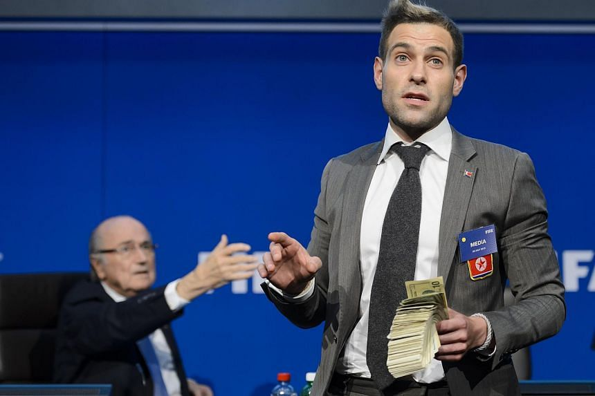 British comedian Lee Nelson (right) holds fake dollar notes next to Fifa president Sepp Blatter as he gestures during a protest at a Fifa press conference.