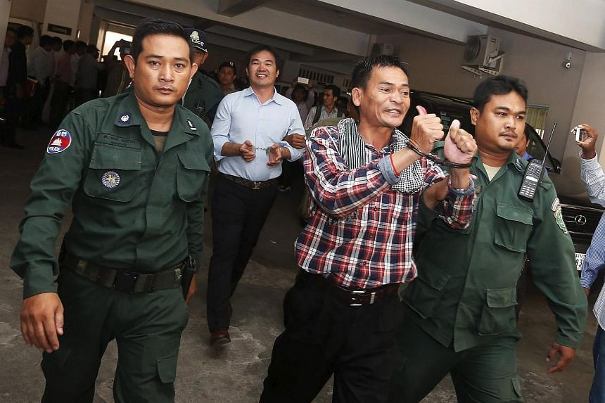 Supporters of the Cambodian National Rescue Party (CNRP) being escorted by Cambodian police officers at the Phnom Penh Municipal Court on July 21, 2015.
