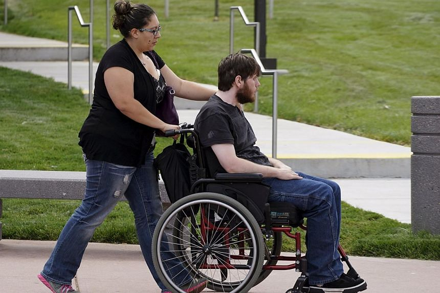 Aurora theatre shooting victim Caleb Medley (in wheelchair) arrives with his wife Katie (pushing him) at the Arapahoe County Courthouse in Centennial, Colorado July 16, 2015 to hear the verdict in the trial.