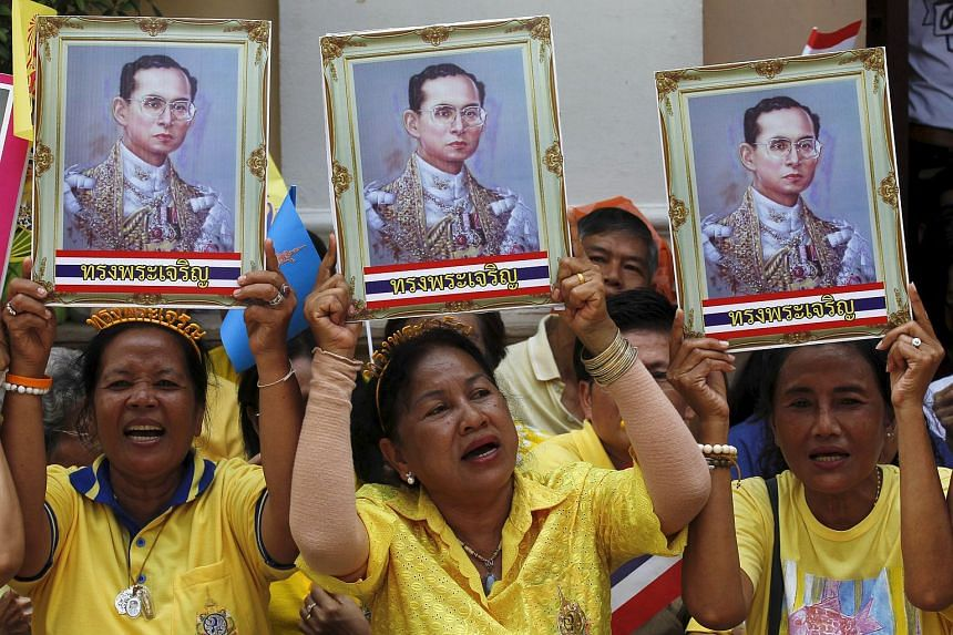 Well-wishers holding up pictures of Thailand's revered King Bhumibol Adulyadej at Siriraj Hospital in Bangkok, Thailand, on May 10, 2015.