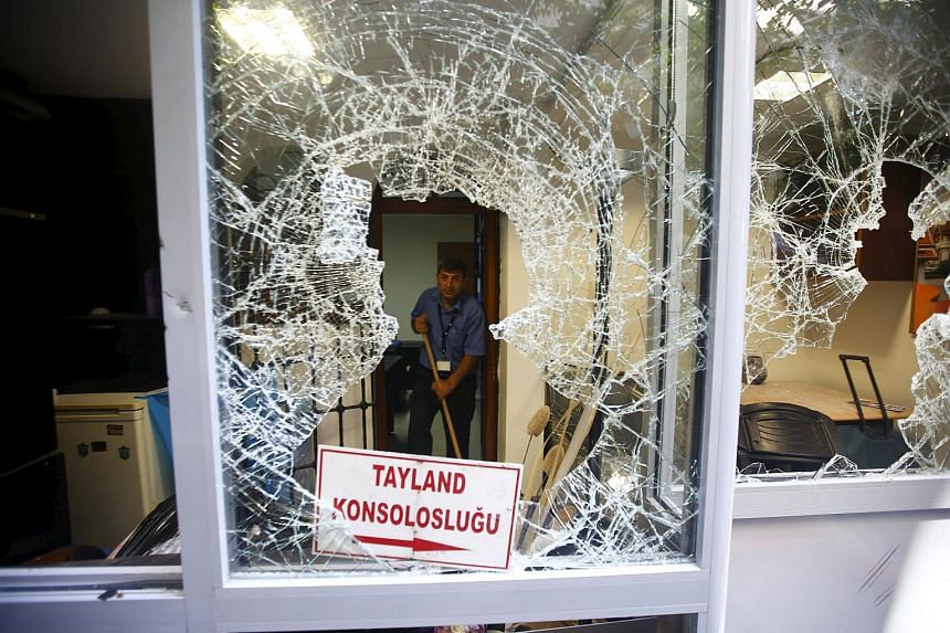 A man removes broken glass from a window of Thai honorary consulate in Istanbul, Turkey on July 9, 2015.