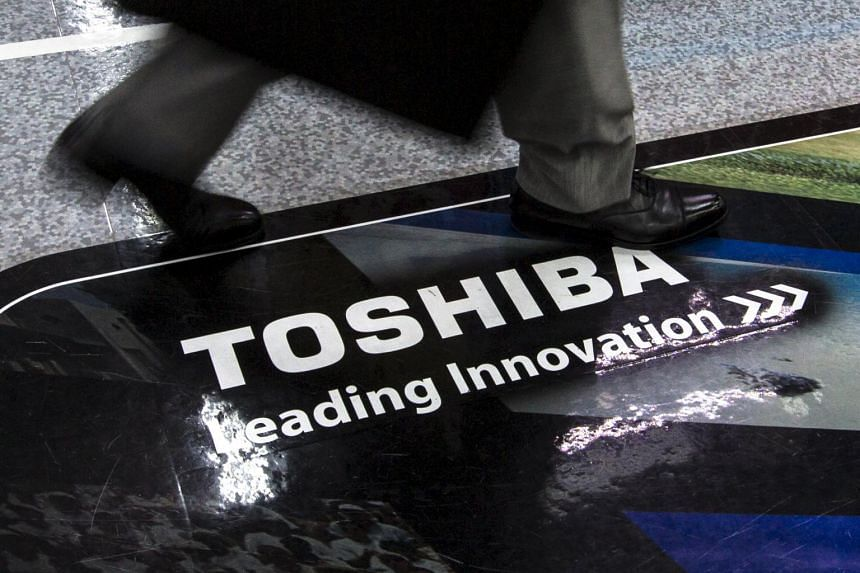 "A man walks past a logo of Toshiba Corp at an electronics store in Tokyo July 21, 2015. Japanese Finance Minister Taro Aso said on Tuesday revelations of accounting problems at Toshiba Corp were ""very regrettable"", adding they could lead to a loss of"