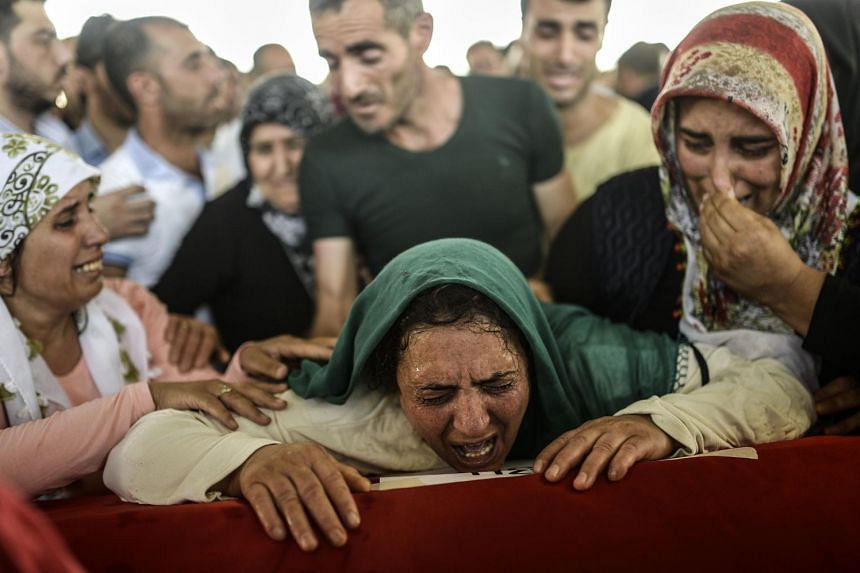 The mother of a victim cries for her son during a funeral ceremony in Gaziantep on July 21, 2015, following a suicide bomb attack the day before which killed at least 31 in the southern Turkish town of Suruc.
