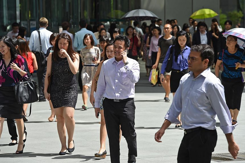 Office workers during lunch time outside Raffles Place MRT station on June 16, 2014.