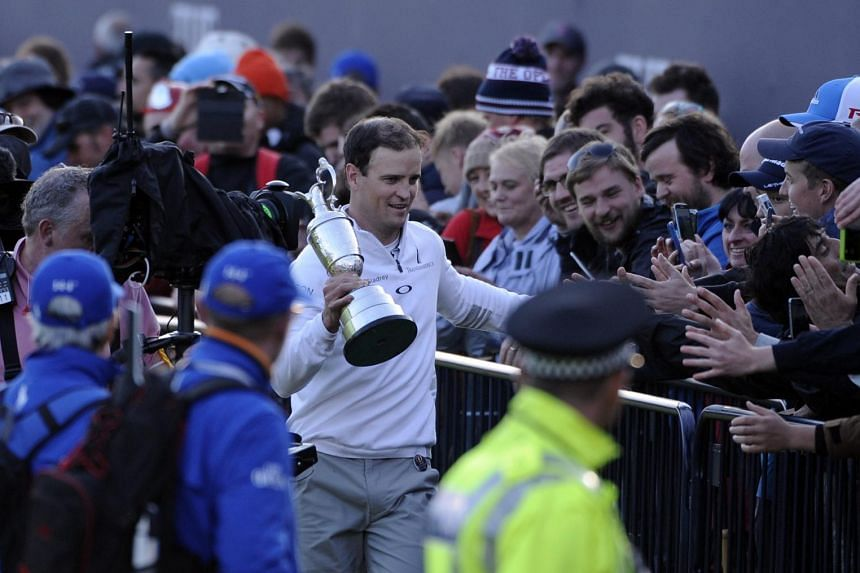 British Open winner Zach Johnson greeting the fans at St Andrews as he holds the Claret Jug.