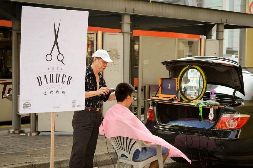 A barber giving a street haircut in a parking lot during Park(ing) Day in 2014.