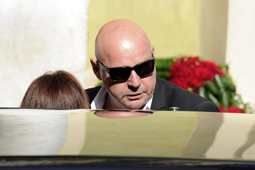 Philippe Bianchi, the father of late French Formula One driver Jules Bianchi, reacts as he pays his last respect to his son's coffin after his funeral ceremony outside Cathedrale Sainte Reparate in Nice on July 21, 2015.