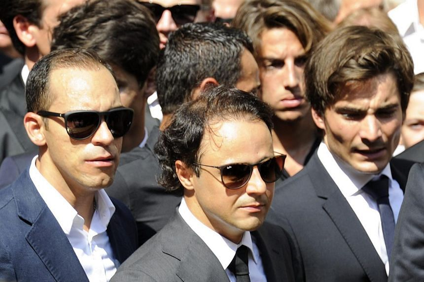 Formula One racing drivers Venezuelan Pastor Maldonado (left) and Brazilian Felipe Massa (centre) attend the furneral of late French Formula 1 driver Jules Bianchi at the Cathedrale Sainte Reparate in Nice, France, on July 21, 2015.
