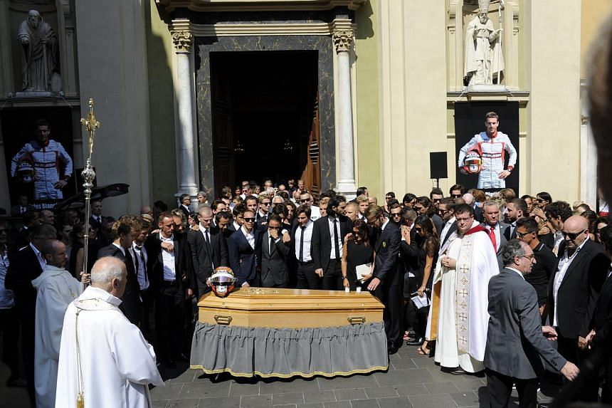 Formula One racing drivers alongside late French Formula 1 driver Jules Bianchi's helmet on his coffin after his funeral ceremony outside the Cathedrale Sainte Reparate in Nice, France, on July 21, 2015.