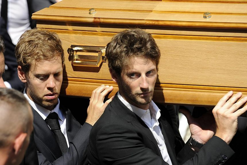 German Formula One driver Sebastian Vettel (left) and French Formula One driver Romain Grosjean (right) join pallbearers carrying the coffin of French Formula One driver Jules Bianchi during the funeral held at the Cathedral of Sainte Reparate, in Ni