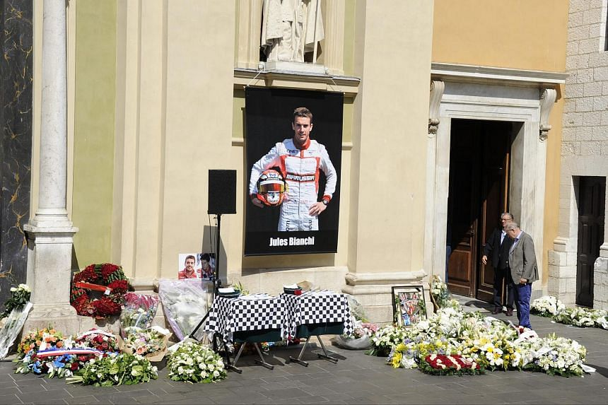 Morners pause to view the wreaths as they arrive for the funeral ceremony of French Formula One driver Jules Bianchi held at the Cathedral of Sainte Reparate, in Nice, France, on July 21, 2015.
