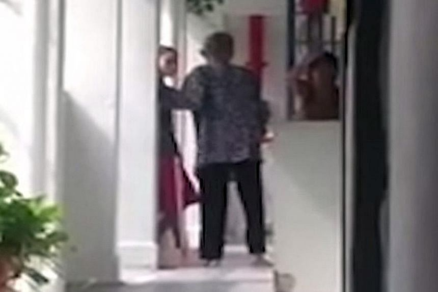 Stills from the video, which has gone viral on social media, showing the alleged abuse of a frail-looking woman by one of the two younger women watching her as she was sweeping the floor in the corridor outside a Housing Board unit in Lower Delta Roa