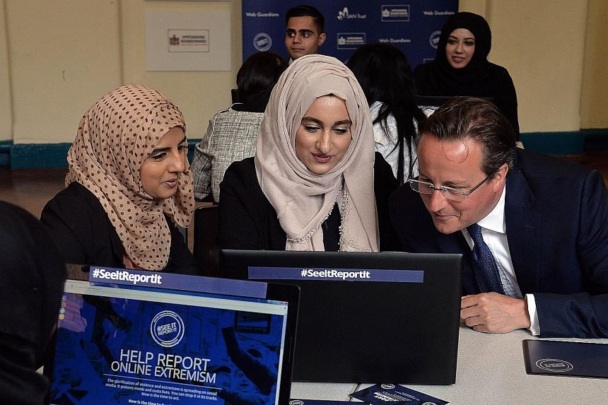 British PM David Cameron looking at a computer with Ms Aysha Iqbal Patel (far left) and Ms Zahra Qadir during a workshop about ways to report suspicious online activity, at Ninestiles Academy in Birmingham, central England, on Monday.