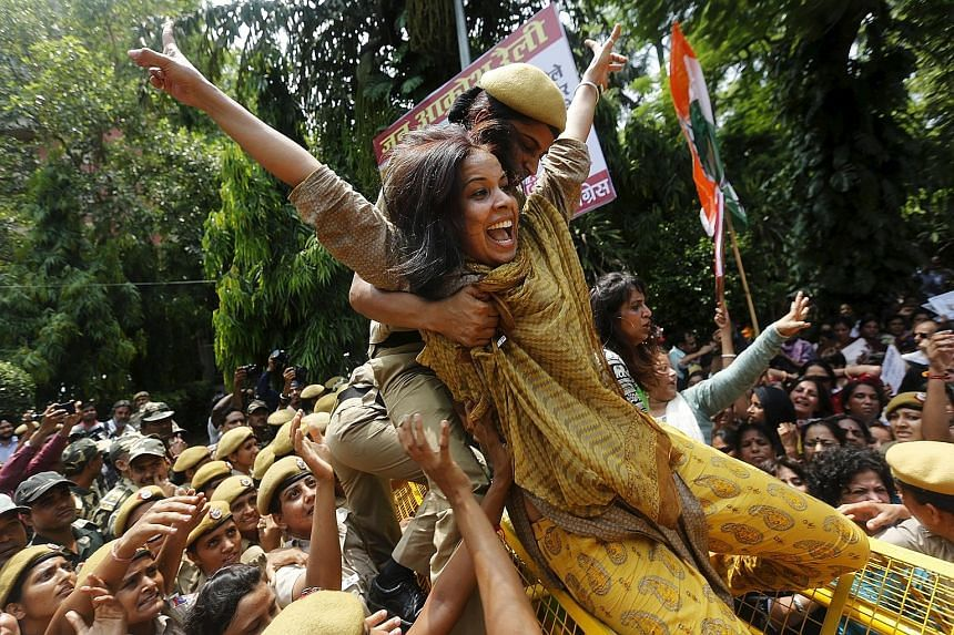 A policewoman trying to stop a member of the All India Mahila Congress from crossing a barricade during a protest against Indian Prime Minister Narendra Modi in New Delhi yesterday. Mr Modi's government aims to push through reforms to revive the econ