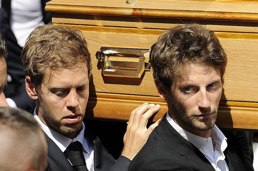 Formula One drivers Sebastian Vettel (left) and Romain Grosjean join pallbearers carrying the coffin of Jules Bianchi during his funeral in Nice yesterday.
