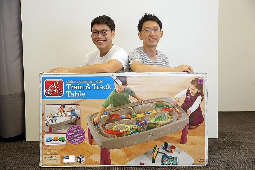 Airfrov founder Cai Li (far left) and Robi with a massive toy train set from the US which was requested by a user of their site - and lugged back to Singapore by another user.