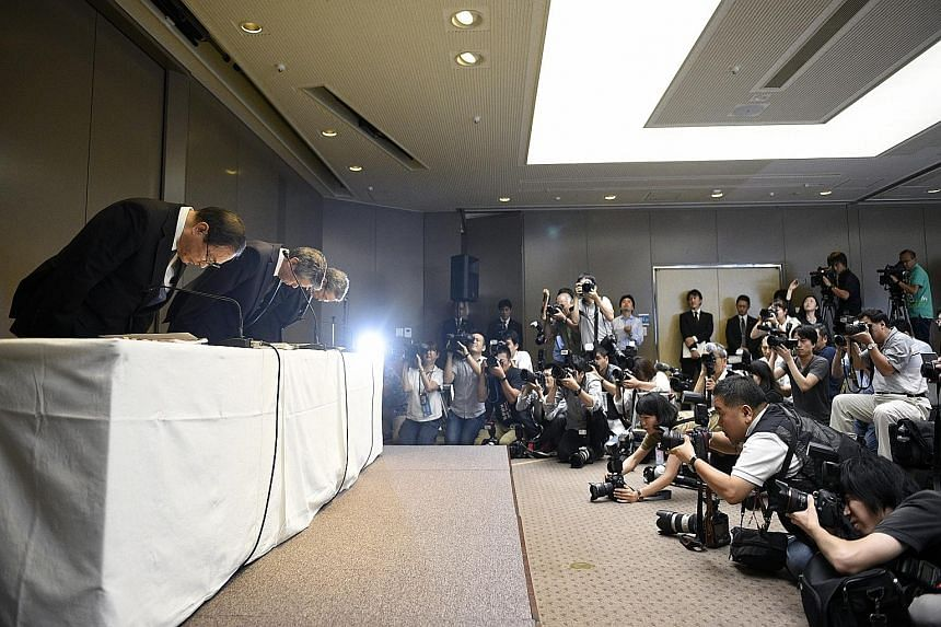 Toshiba president Hisao Tanaka (centre), chairman Masashi Muromachi (left) and executive officer Keizo Maeda bowing during a press conference yesterday at the company's headquarters in Tokyo. Three executives resigned to take responsibility for a US$