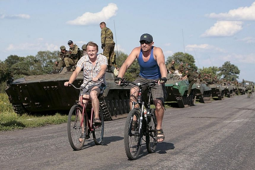 Men riding past an armoured column of the self-proclaimed Donetsk People's Republic forces yesterday near the site of the MH17 plane crash outside the village of Hrabove in Donetsk region, Ukraine. Ukraine and Western countries accuse the rebels of s