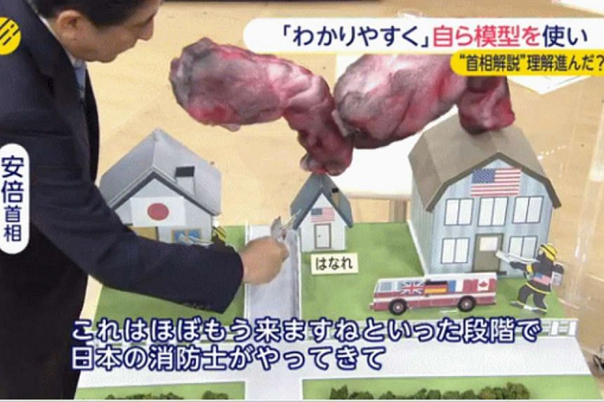Japanese Twitter users were howling in derision Wednesday after Prime Minister Shinzo Abe used paper models and cut-out firefighters on television, in his latest attempt to explain controversial security legislation.