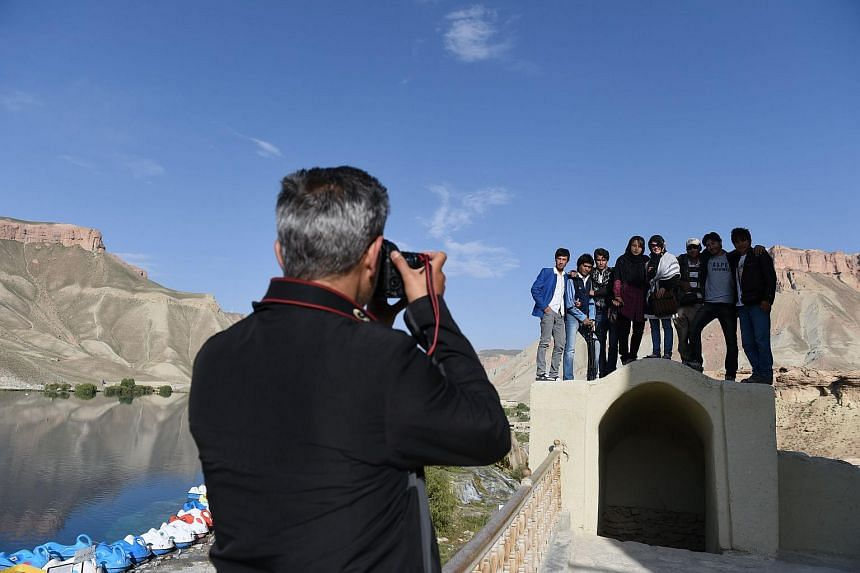 A photographer taking a picture of Afghan youths near Band-i-Amir Lake in the central Afghan province of Bamiyan.