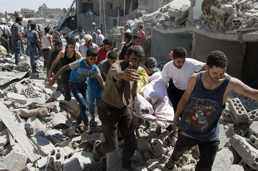 Syrians carry a body after a missile fired by government forces hit Aleppo city on July 21, 2015.