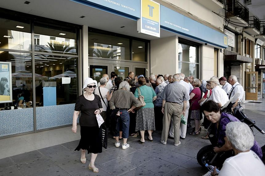 Customers queue to access a Eurobank Ergasias SA bank branch ahead of opening in Thessaloniki, Greece, on July 20, 2015.