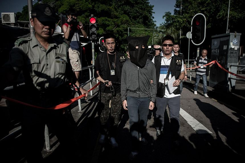 In this photograph taken on on June 16, 2015, a suspect is escorted by policemen during a crime reconstruction in the east-coast district of Sai Kung in Hong Kong.