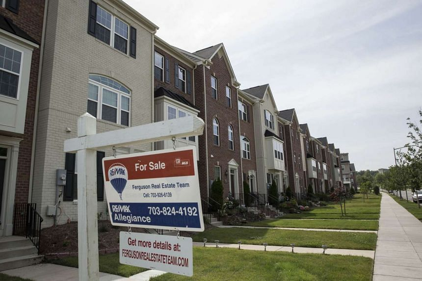 """A """"For Sale"""" sign sits in the front yard of a townhouse June 23, 2015 in Northeast Washington, DC. Purchases of new homes in the U.S. rose in May to the highest level in seven years, signaling that the industry may be gaining momentum heading toward"""