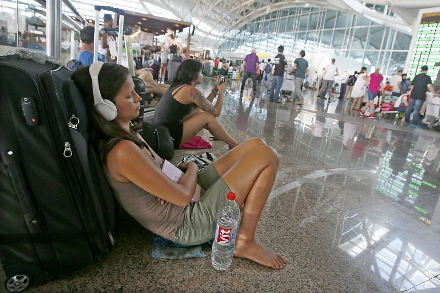 Passengers wait for their delayed flights at Bali's Ngurah Rai International Airport in Bali, Indonesia, on July 12, 2015. Ash spewing from a volcano closed Bali's airport on July 22 for the third time this month, forcing the cancellation of flights