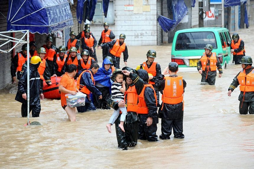 Militia members evacuate residents in a flooded area after torrential rains brought by Typhoon Chan-Hom in Shaoxing in east China's Zhejiang province, on July 11, 2015.