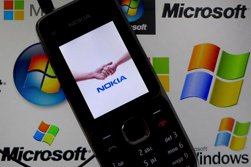 A Nokia mobile phone lies on a tablet computer showing logos of Microsoft.