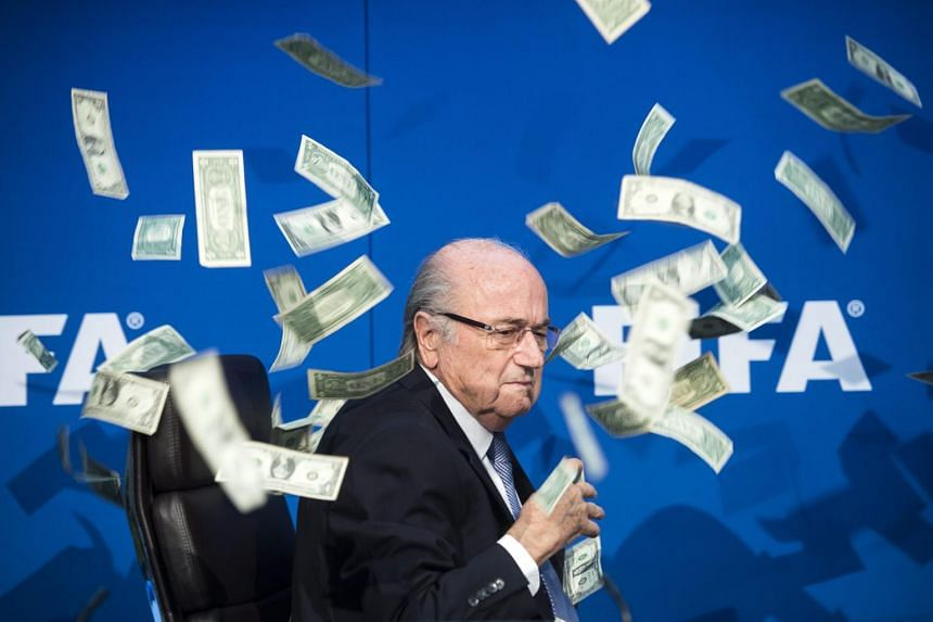 Fifa president Sepp Blatter is showered with fake banknotes.