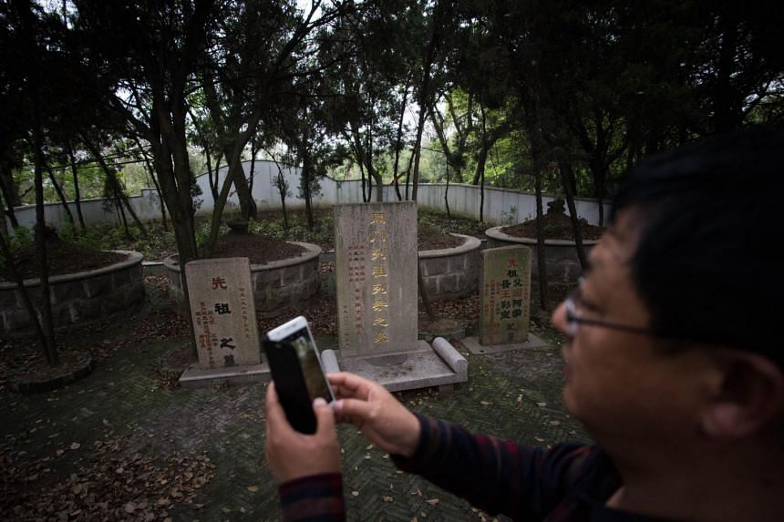 A man taking photographs of the tombstones of the ancestral relatives of China's former security chief Zhou Yongkang, who was jailed for life on June 11.