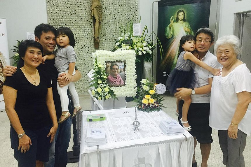 Former Singapore star striker Quah Kim Swee's family - (from left) daughter Bee Jin, youngest son Soon Aun with baby, eldest son Soon Hong with child, and wife Helen - at the wake held at St Joseph's Church.