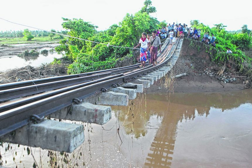 People making their way along a broken, flood- damaged bridge in Kanbalu, Sagaing division, Myanmar, on Tuesday. Monsoon rains have led to floods across the country. Several people have died and thousands are fleeing their homes.