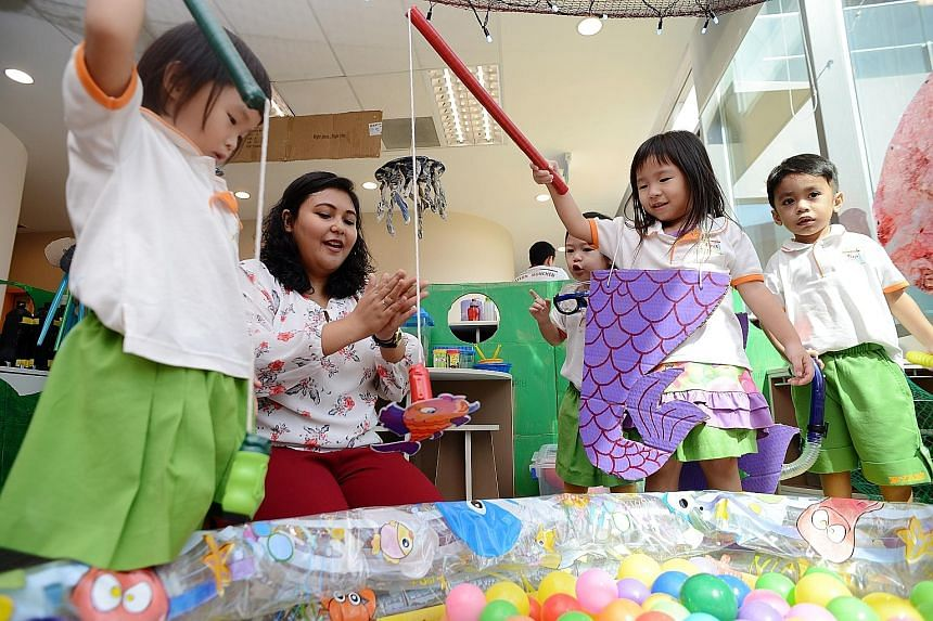 English teacher Qamariza Jamaludin, 31, with some of her charges at the Westgate shopping mall branch of My First Skool, which comes under NTUC First Campus. Under the new curriculum, one teacher is allocated to every two to three children, instead o