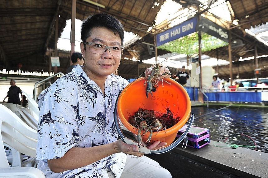 Mr Anthony Lim, with a bucket of river crayfish straight out of the pond.