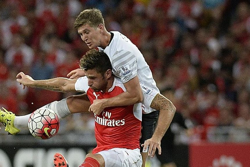 Jose Mourinho thinks young English talents like Raheem Stirling and Luke Shaw are overpriced but is willing to splurge the cash on Everton's John Stones (right, in a tussle with Arsenal forward Olivier Giroud).