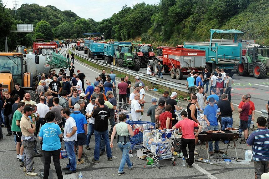 Farmers using tractors to block a highway in Quimper, north-western France, on Tuesday during a demonstration against the falling prices of their produce. Foreign competition and changing diets - people are eating less meat - have driven down pork, b