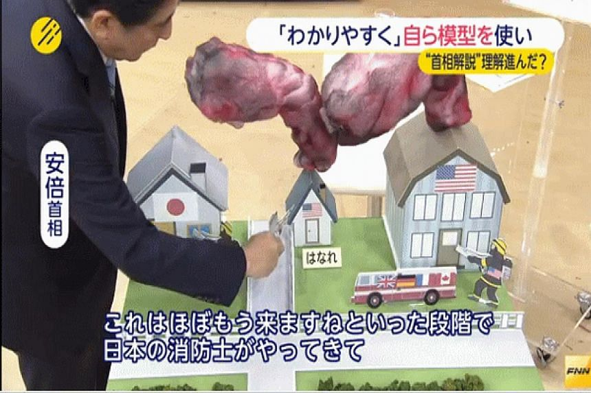 Prime Minister Shinzo Abe using paper models and cut-out firefighters on television to try to explain his security Bills - an attempt mocked by many Japanese.