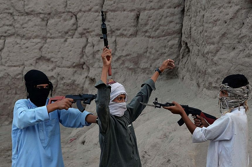 Afghan children playing with plastic guns as they celebrate the second day of Eid al-Fitr, which marks the end of the Muslim fasting month of Ramadan, on the outskirts of Jalalabad city in eastern Nangarhar province. Afghanistan banned the sale of im