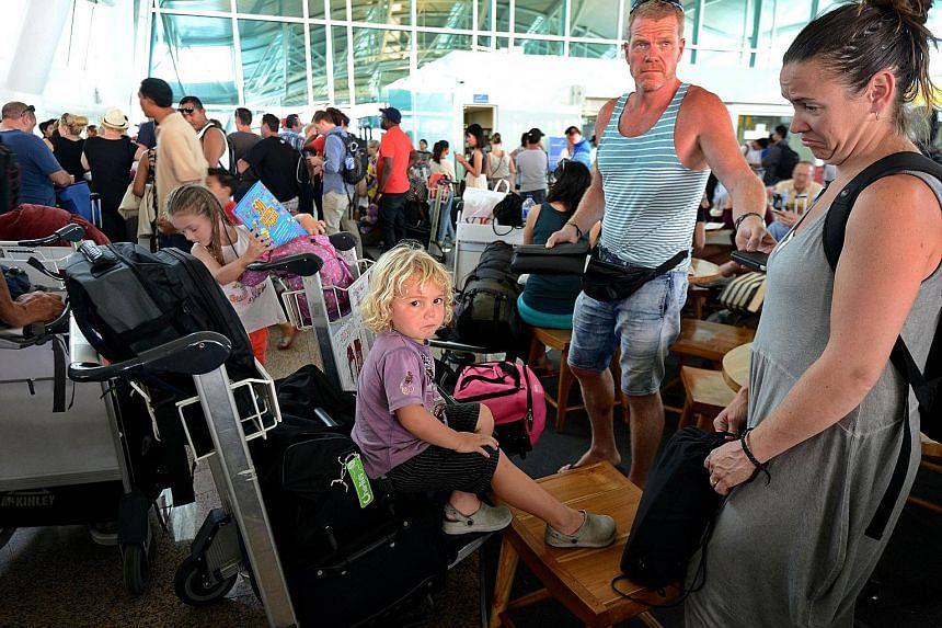 Passengers at Bali's Ngurah Rai airport waiting for information about delayed flights yesterday. The shutdown was brief, with the airport reopening around two hours later as the ash was blown away.