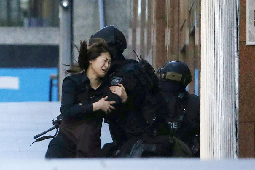 A hostage runs towards a police officer outside Lindt cafe, during the hostage crisis in central Sydney on Dec 15, 2014.