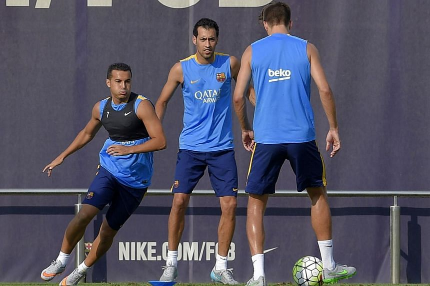 Barcelona's forward Pedro Rodriguez (left), Barcelona's midfielder Sergio Busquets (centre) and Barcelona's defender Gerard Pique take part in a training session.