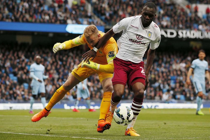 Benteke (right) in action for Aston Villa against Manchester City's Joe Hart.