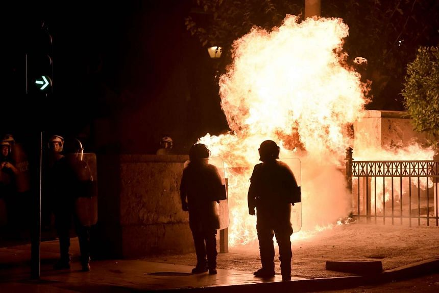 A fire bomb explodes behind riot police.