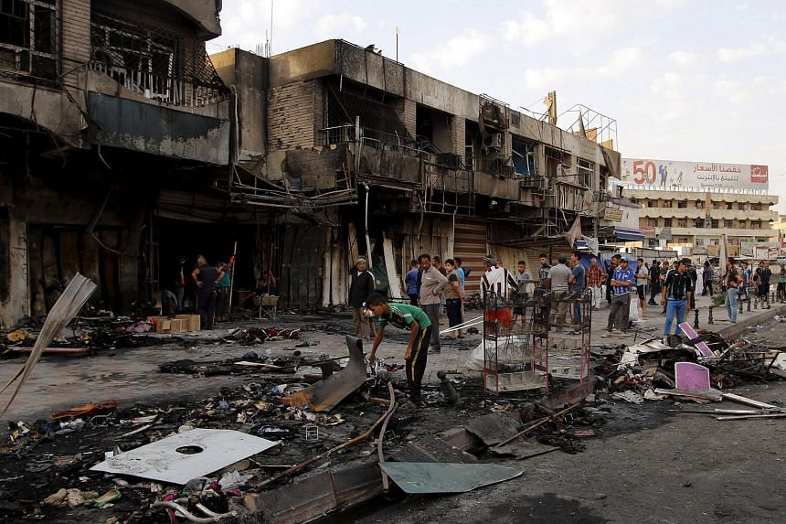 People gather at the site of a car bomb attack in New Baghdad, on July 22, 2015.