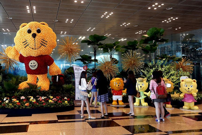 People walk past an exhibit of Singa the Courtesy Lion, the mascot of the Singapore Kindness Movement, in Changi Airport on July 15, 2015.