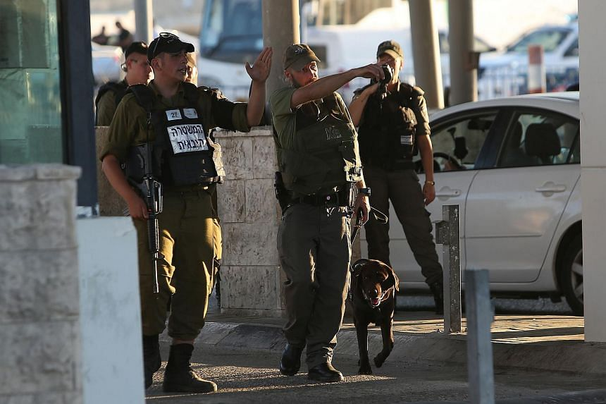 Israeli soldiers stand at the Qalandia checkpoint between Jerusalem and and the West Bank city of Ramallah on June 30, 2015.
