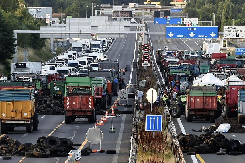 Farmers block the A6 motorway with tractors, farm trailers and tyres at the northern entrance to Lyon, on July 23, 2015.